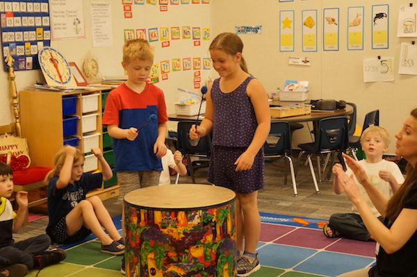 Two children playing the drum