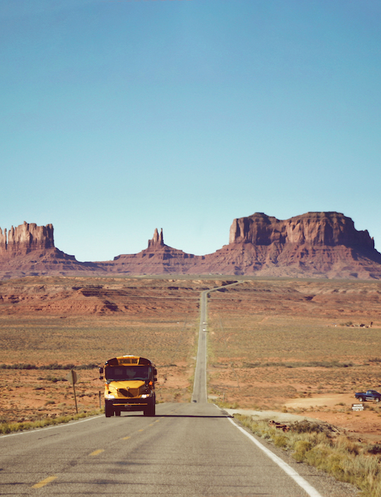 Yellow bus against the backdrop of rural Utah