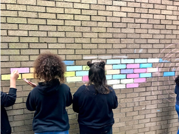 Campers at Grantham Academy are allowed to be creative with chalk and make colorful chalk art on the wall of the school courtyard. Photo by Russell Stephenson.