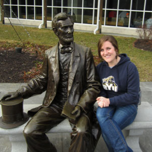 Anna Herring sitting next to a statue of Abraham Lincoln