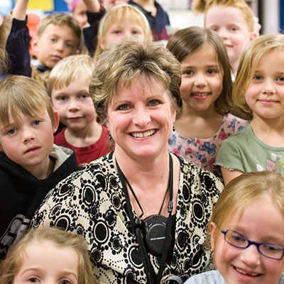 A teacher surrounded by her class.