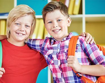 Two boys with backpacks on and arms around each others shoulders