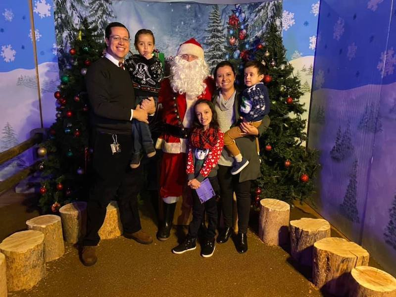family standing with Santa Claus