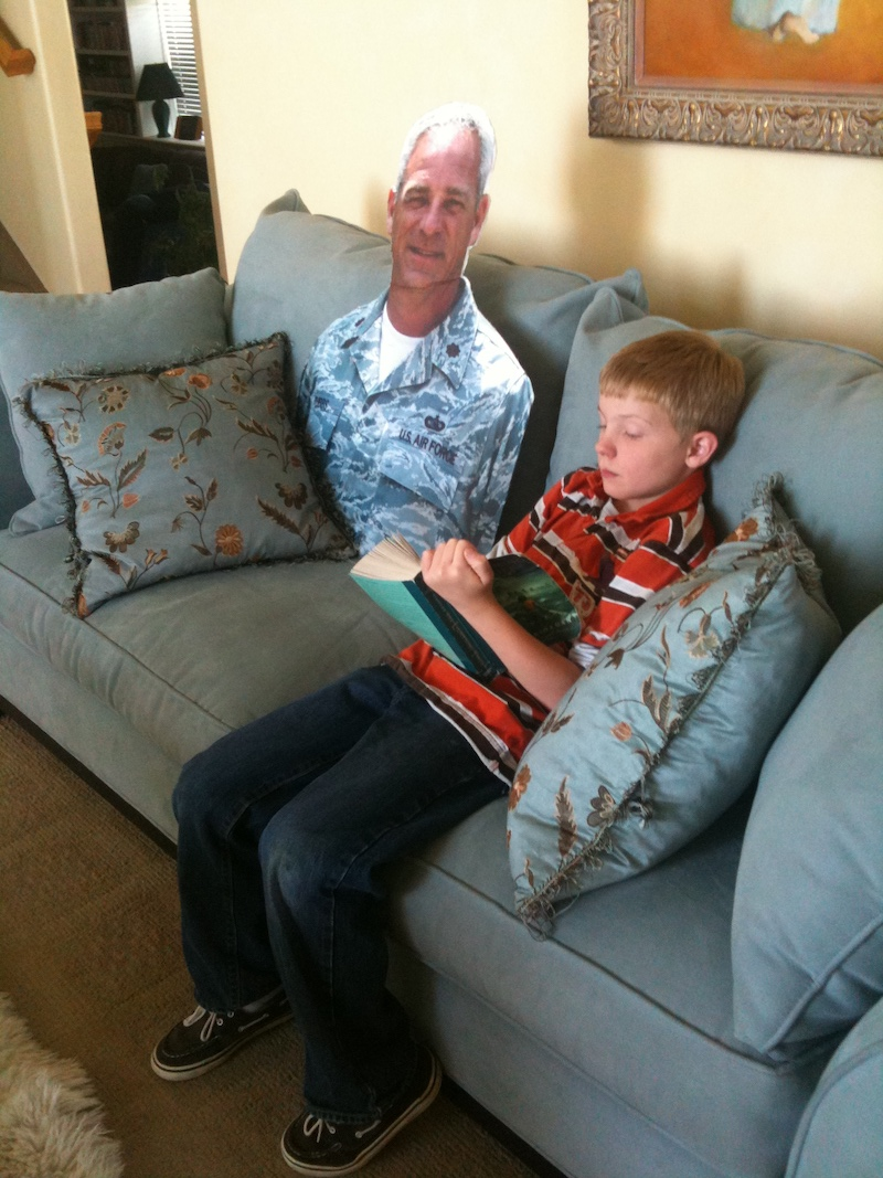 Child reading to cardboard cutout of father.